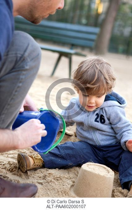 Toddler boy playing in sand with his father