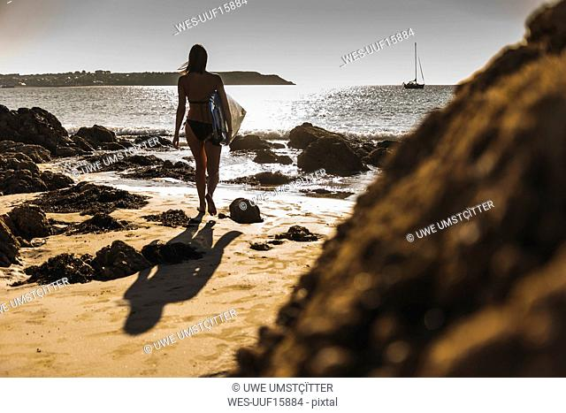 France, Brittany, young woman carrying surfboard on a rocky beach at the sea
