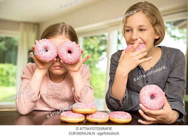 Two sisters one with doughnut holes over her eyes, the other eating