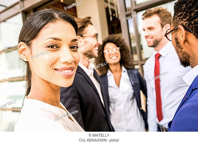 Portrait of young businesswoman and team outside office