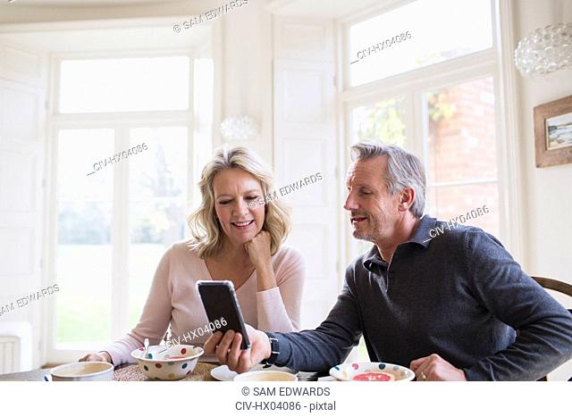Mature couple using smart phone at breakfast table