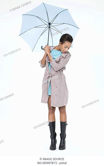 Young woman holding umbrella and looking down
