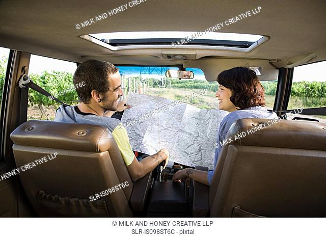 Young couple in vehicle with map