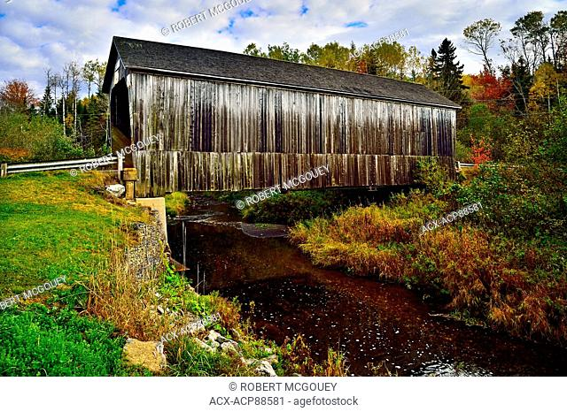An autumn landscape view of the iconic wooden covered bridge spanning the Wards Creek near Sussex New Brunswick Canada