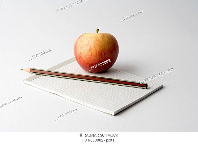 Apple and pencil on top of note pad