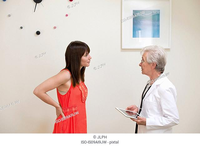 Mature woman questioning female doctor face to face in doctors office