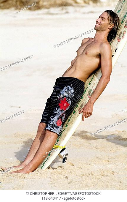 young man leaning to surfboard