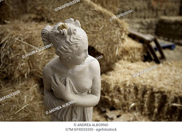 Statue of a female amongst bales of hay and other furniture