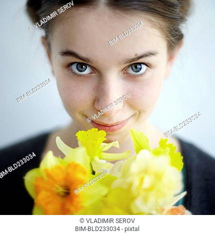 Smiling Caucasian girl holding yellow flowers
