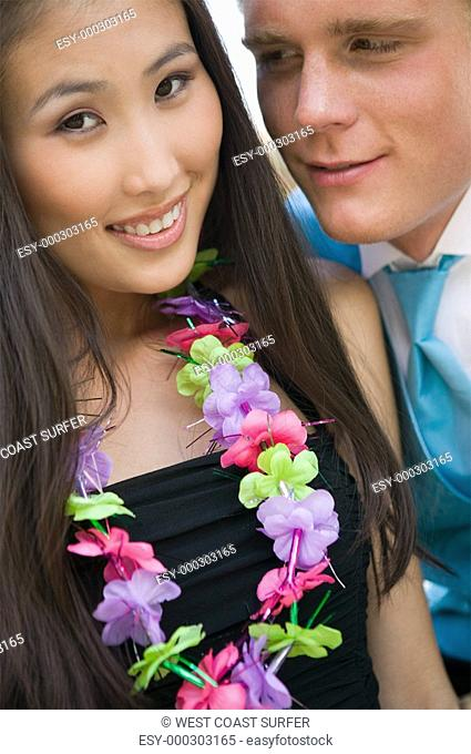 Well-dressed teenage couple wearing leis outside school dance