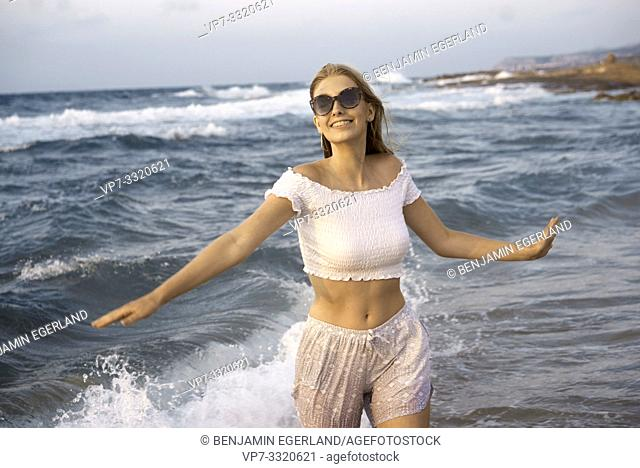 young woman enjoying holiday at beach, open arms, in Crete, Greece