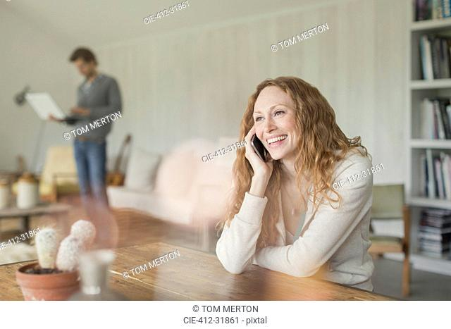 Smiling woman talking on cell phone at dining table