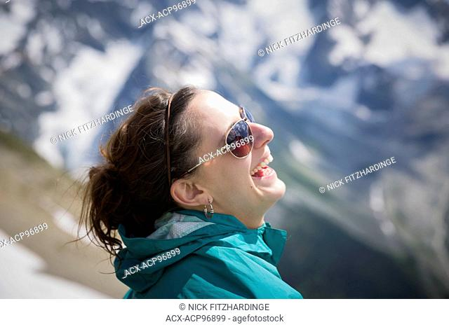 Female with sunglasses in aqua jacket laughing, British Columbia, Canada