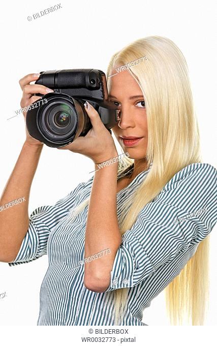 Young woman takes photo with a digital SLR camera