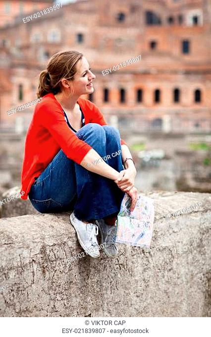 Pretty young female tourist studying a map (Rome, Italy)
