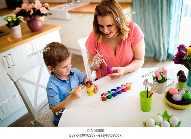 Happy young mother and son are sitting at a table painting Easter egg