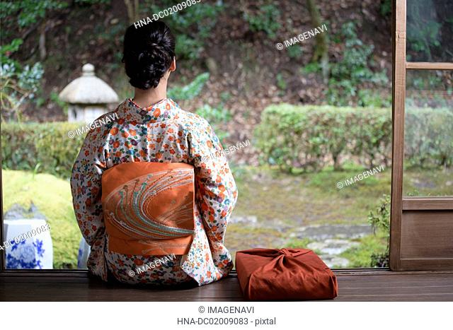 Young Japanese woman in kimono and parcel
