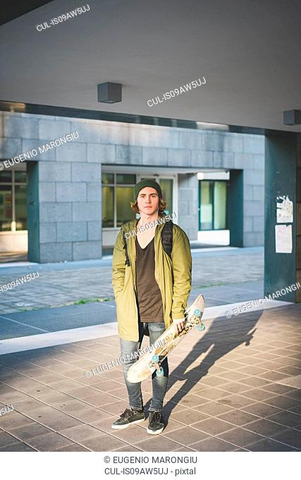 Portrait of cool young male urban skateboarder holding skateboard