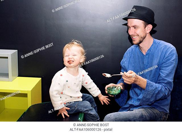 Father feeding toddler ice cream