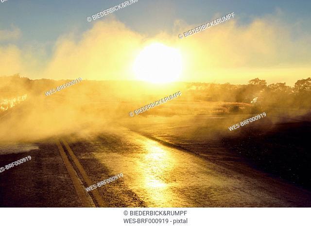 USA, Hawaii, Big Island, Volcanoes National Park, sulfur vapor over lane in morning twilight at Steaming Bluff