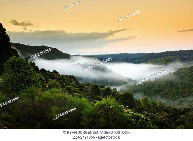 Fine art landscape photo on a misty morning view with an orange sunrise over Waratah Mountains in Tasmania, Australia. Valley daybreak
