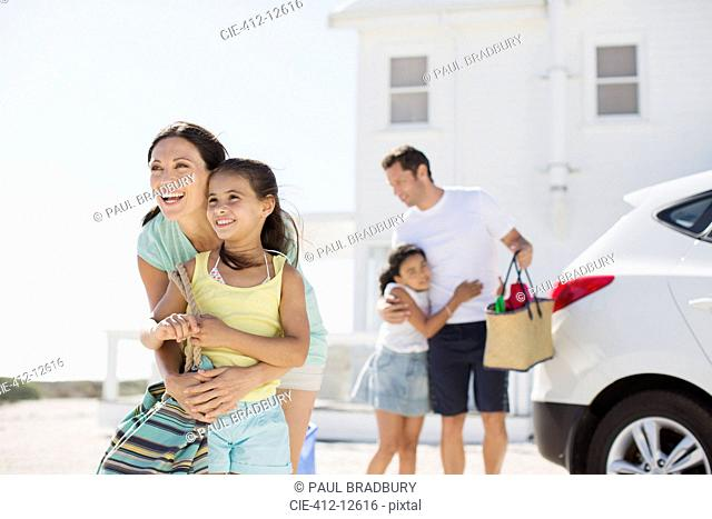 Family hugging in sunny driveway