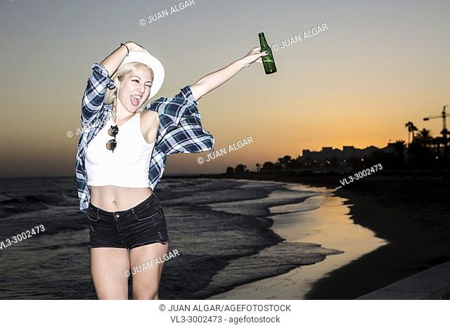 Cheerful young woman hanging out with bottle of beer at seaside in the evening. Lanzarote, Canary Islands, Spain