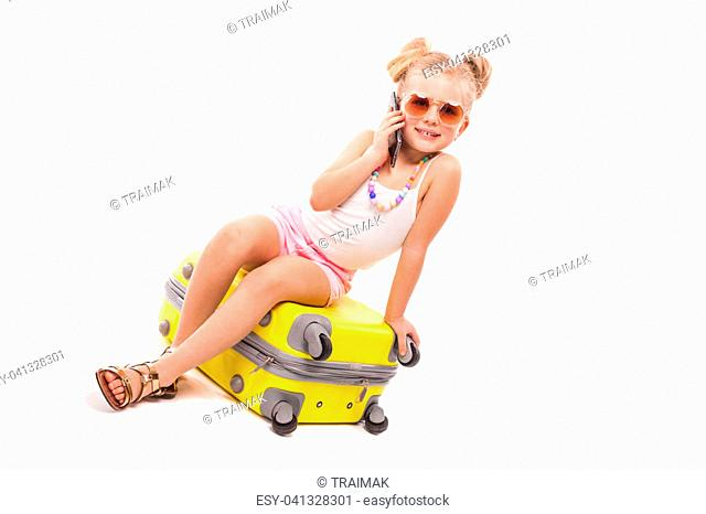 Isolated on white, pretty little caucasian blonde girl in white shirt, pink shorts, sunglasses and sandals sit on the yellow suitcase, look at camera