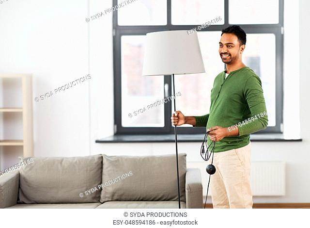 happy indian man holding floor lamp at home