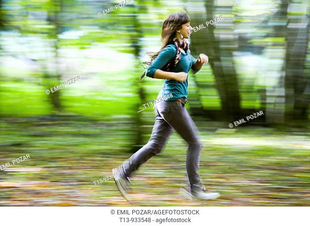Running young woman in forest, panning photo