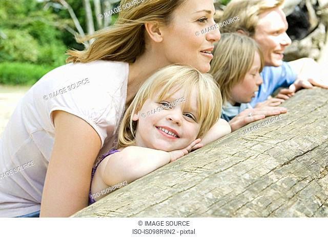 Family leaning on a log