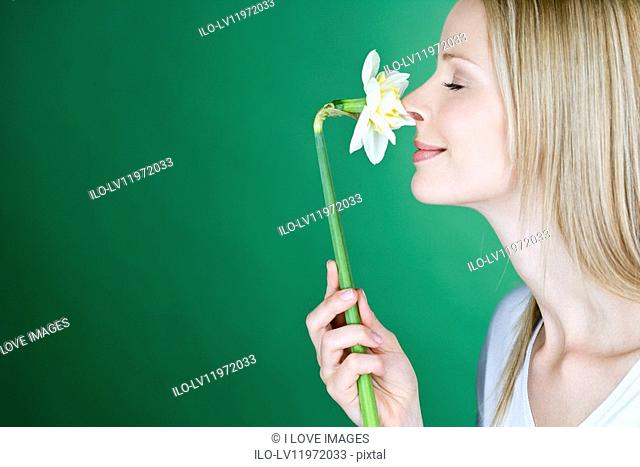 A young blonde woman smelling a daffodil, side view