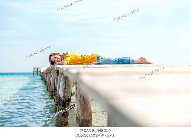 Portrait of mid adult woman lying on pier