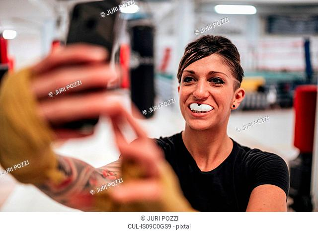 Boxer taking selfie wearing gumshield in gym