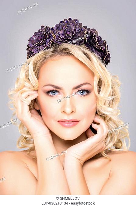 Close-up of young, sensual woman wearing purple flower alike coronet over grey background