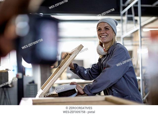Smiling woman working on frame in workshop