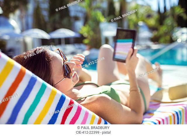 Smiling woman with digital tablet sunbathing by swimming pool