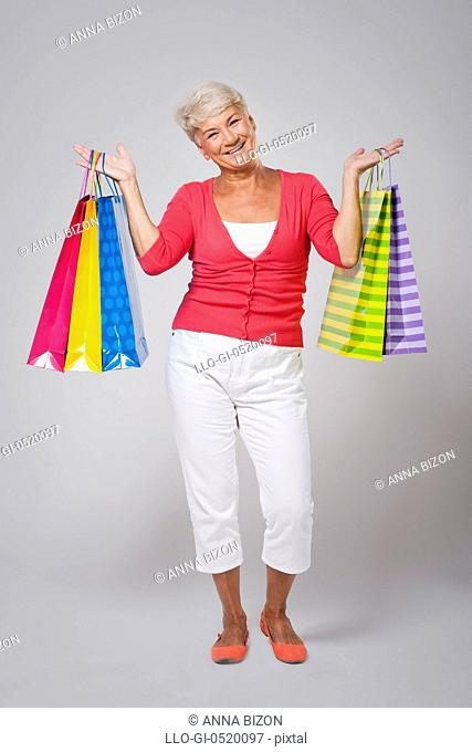 Portrait of senior woman with shopping bags. Debica, Poland