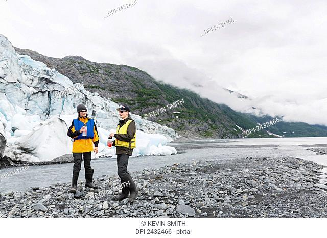 Teenage boys standing in front of Shoup glacier and Chugach mountains, Shoup Bay State Marine Park, Prince William Sound; Valdez, Alaska
