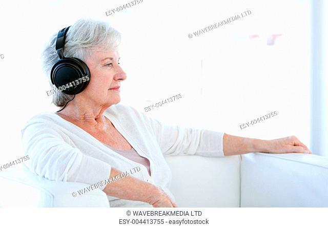 Senior woman listening music with headphones
