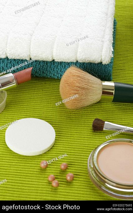 Make-up powder and brush on the green background