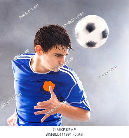 Hispanic soccer player hitting ball with head