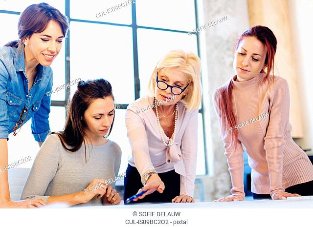 Four women in business meeting, looking at document