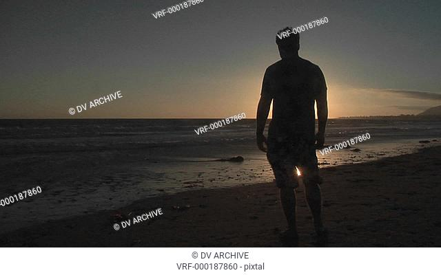 A man stands alone on a windy beach
