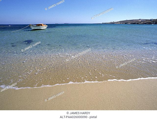 Greece, Cyclades, seashore with small anchored boat