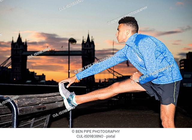 Man stretching by riverside, Tower Bridge in background, Wapping, London, UK