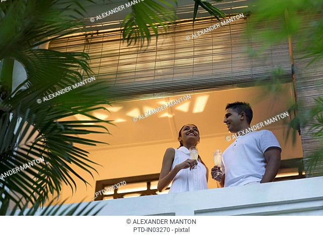 Singapore, Two young people standing on balcony, holding champagne