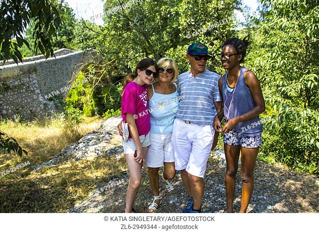 Grandparents on a family vacation in the south of france with grandchildren. Caucasian grandparents taking photos with their teenager granddaughters: One...