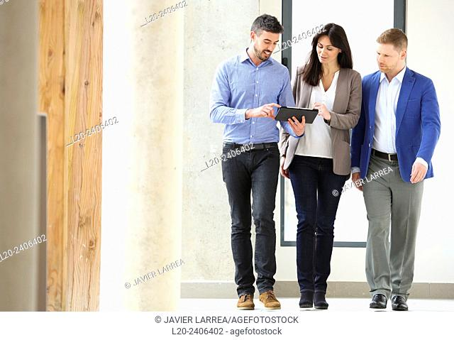 Three executives looking at tablet