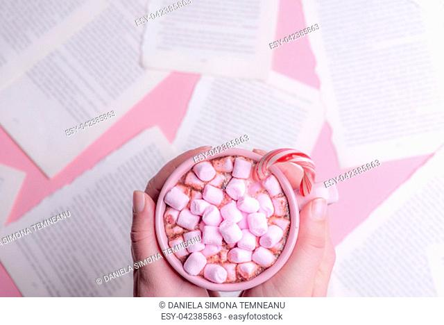 Woman holding in her hands a cup of hot chocolate with pink mini marshmallows and an Xmas candy cane, over a table with book pages